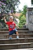 Het kind beklimt onderaan treden Stock Foto's