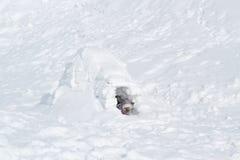 Het kind beklimt uit het iglo-Sneeuw hol dat naar huis aan de Eskimo's is royalty-vrije stock foto's