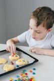 Het kind bereidt eigengemaakte Kerstmiskoekjes voor royalty-vrije stock afbeeldingen