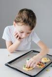 Het kind bereidt eigengemaakte Kerstmiskoekjes voor stock foto's