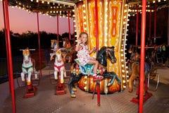 Het kind berijdt een carrousel Stock Foto's