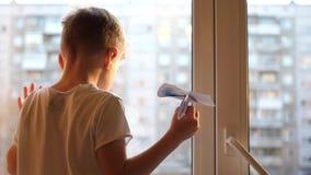 Het kind bevindt zich bij het venster en houdt een document vliegtuig De dag van de winter stock videobeelden
