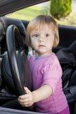 Het kind bij het wiel de auto stock fotografie