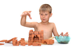 Het kind bouwt een plattelandshuisje gemaakt ââof tot bakstenen Stock Afbeelding