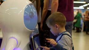 Het kind communiceert met de robot Moderne robotachtige technologieën Kunstmatige intelligentie Cybernetische systemen vandaag stock footage