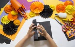 Het kind creeert een giftdoos van een zwarte kat Een partij voor Halloween stock fotografie