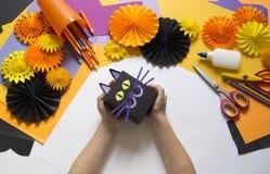 Het kind creeert een giftdoos van een zwarte kat Een partij voor Halloween stock afbeelding