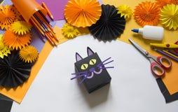 Het kind creeert een giftdoos van een zwarte kat Een partij voor Halloween royalty-vrije stock afbeeldingen