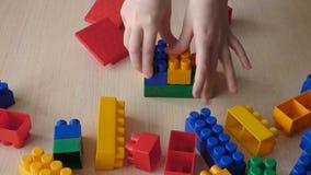 Het kind creeert stuk speelgoed het buiding van plastic blokken stock videobeelden