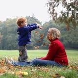 Het kind dat de herfst werpt doorbladert Stock Afbeeldingen