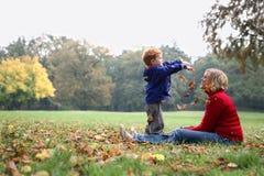 Het kind dat de herfst werpt doorbladert Stock Foto