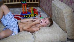 Het kind dat pret op de hoofdkussens en de lach heeft stock videobeelden