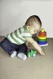 Het kind dat van de baby met speelgoed met speelgoed speelt Stock Foto's