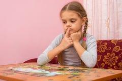 Het kind denkt hoe te om een beeld van raadsels te assembleren Royalty-vrije Stock Afbeelding