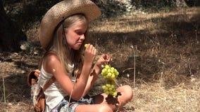 Het kind die druiven eten, hongerig toeristenmeisje eet vruchten in olijfboomgaard 4K stock footage