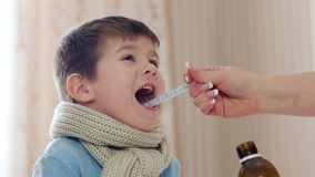 Het kind die hoeststroop nemen, weinig jongen is ziek, geeft het Mamma de temperatuur van de zoonsstroop, medicijn tijdens ziekte stock video