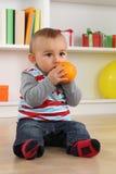 Het kind die van de babyjongen oranje fruit eten Stock Fotografie