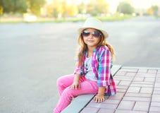 Het kind die van het maniermeisje een geruite roze overhemd, een hoed en zonnebril dragen Royalty-vrije Stock Foto's