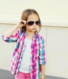 Het kind die van het maniermeisje een roze geruit overhemd en zonnebril dragen Stock Foto
