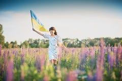 Het kind draagt fladderende blauwe en gele vlag van de Oekraïne stock afbeeldingen