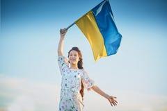 Het kind draagt fladderende blauwe en gele vlag van de Oekraïne op gebied Ukraine& x27; s Onafhankelijkheidsdag De Dag van de vla stock afbeeldingen