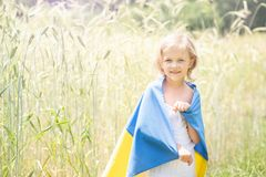 Het kind draagt fladderende blauwe en gele vlag van de Oekraïne op tarwegebied Ukraine& x27; s Onafhankelijkheidsdag De Dag van d royalty-vrije stock afbeeldingen