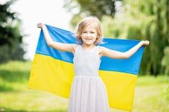 Het kind draagt fladderende blauwe en gele vlag van de Oekraïne op tarwegebied Ukraine& x27; s Onafhankelijkheidsdag De Dag van d stock foto
