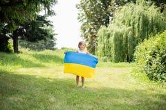 Het kind draagt fladderende blauwe en gele vlag van de Oekra?ne op gebied De Onafhankelijkheidsdag van de Oekra?ne ` s De Dag van royalty-vrije stock foto's