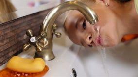 Het kind drinkt water van de badkamerstapkraan stock video