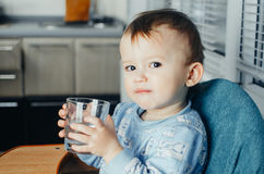 Het kind drinkt water van een glas stock foto's