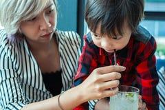 Het kind drinkwater van de mammahulp van stro tussen het werken stock fotografie