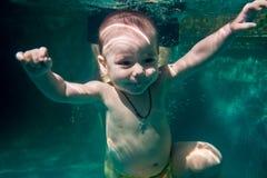 Het kind duikt onder het water in de pool gecombineerd met een bus stock foto