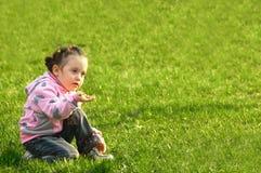 Het kind een ruikende bloem in een groen gras Royalty-vrije Stock Afbeeldingen