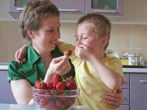 Het kind eet aardbeien te veel royalty-vrije stock afbeelding