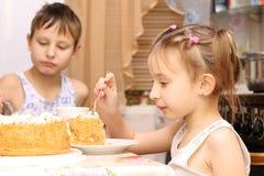 Het kind eet bij de lijst Stock Afbeelding