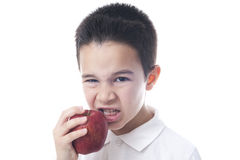 Het kind eet een appel met boos gezicht Stock Foto's