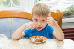 Het kind eet een dessert Stock Afbeelding