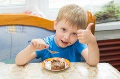 Het kind eet een dessert Stock Afbeeldingen