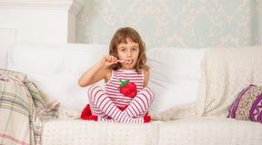 Het kind eet een gestreept suikergoed stock afbeeldingen