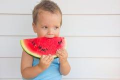 Het kind eet een watermeloen royalty-vrije stock afbeelding