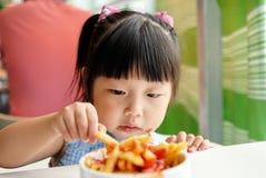 Het kind eet gebraden gerechten Stock Afbeeldingen