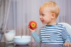 Het kind eet havermoutpap Blauwe ogen van de jong geitje zitten de leuke jongen bij lijst met plaat en voedsel Gezond voedsel Jon royalty-vrije stock afbeeldingen