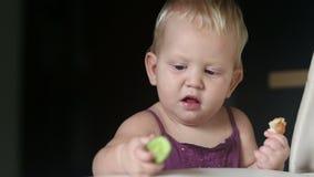 Het kind eet komkommer die zich voor een bank bevinden stock video