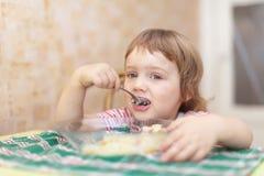 Het kind eet met lepel Stock Fotografie