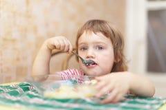 Het kind eet met lepel in huis Royalty-vrije Stock Foto's