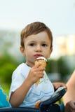 Het kind eet smakelijk roomijs Stock Foto's