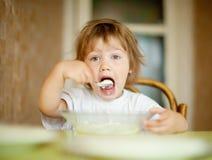 Het kind eet zuivelfabriek met lepel Stock Afbeelding