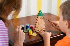 Het kind en de Moeder schilderen een houten Nieuwjaar` s Kerstboom Weinig jongen en moeder trekken een nieuw-jaarboom Stock Fotografie