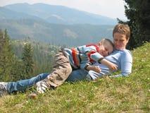 Het kind en de moeder spelen op gras stock afbeeldingen
