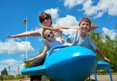 Het kind en de vrouw vliegen op blauwe vliegtuigaantrekkelijkheid in park, gelukkige familie die pret, het concept van de de zome Royalty-vrije Stock Afbeelding